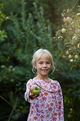 Portrait of smiling girl offering an apple - p300m2114475 by Jana Fernow