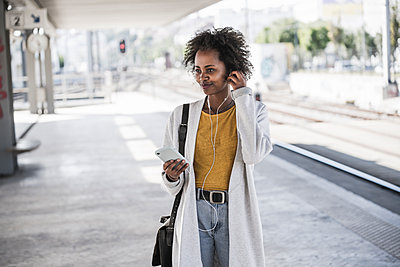 Young woman with cell phone and earphones at the train station - p300m2160727 by Uwe Umstätter