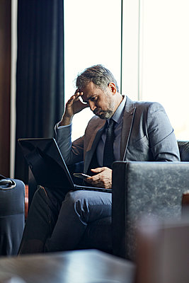Businessman using laptop and smartphone in hotel lobby - p300m2171392 by Zeljko Dangubic