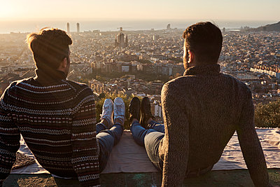 Gay couple sitting on observation point with view of cityscape, Bunkers del Carmel, Barcelona, Spain - p300m2257346 by Veam