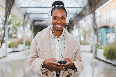 Young black woman listening to music on headphones, Seville, Spain - p300m2275553 von Julio Rodriguez