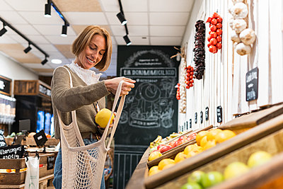 Woman collecting fruit in mesh bag while shopping in supermarket - p300m2286899 by NOVELLIMAGE