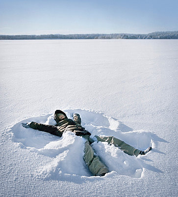Young woman making a snow angel - p3740740 by Lauri Rotko