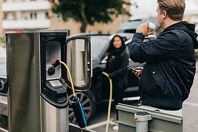 Man drinking coffee while standing at electric car charging station - p426m2195039 by Maskot