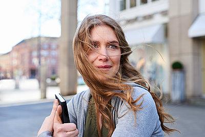 Frau mit wehenden Haaren in der Stadt - p890m1440015 von Mielek
