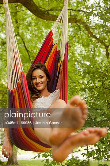 Gutgelaunt in Hängematte relaxen - p045m1169936 von Jasmin Sander