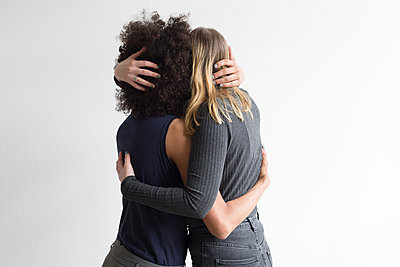 Two young women embracing - p1301m2020247 by Delia Baum