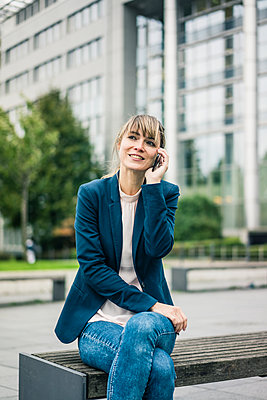 Smiling businesswoman sitting on bench talking on cell phone outdoors - p300m1536168 by Joseffson