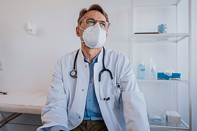 Thoughtful doctor with protective face mask looking away while sitting in clinic - p300m2266862 by Mareen Fischinger