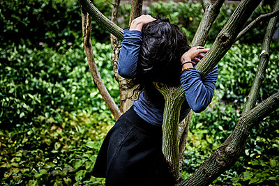 Woman hiding between branches of a tree - p491m2260366 by Ernesto Timor