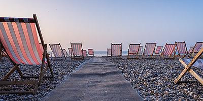 Deckchairs on the popular pebble beach at Beer near Seaton, Devon, England, United Kingdom - p871m2113753 by Baxter Bradford