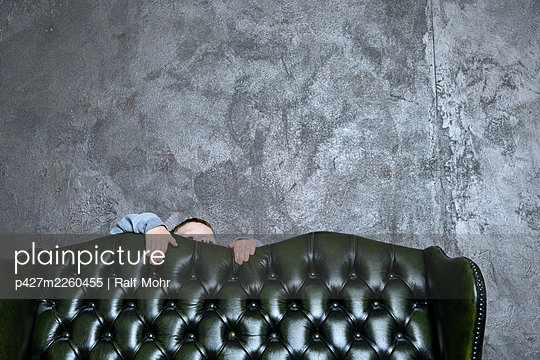 Little boy behind leather sofa - p427m2260455 by Ralf Mohr