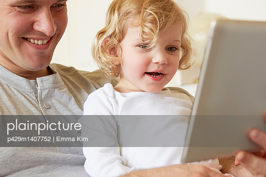 Female toddler sitting on father's knee using digital tablet - p429m1407752 by Emma Kim