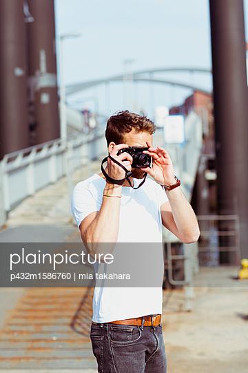 Mann macht Fotos mit Digitalkamera - p432m1586760 von mia takahara