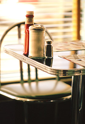 Sugar , pepper salt and ketchup on table in retro diner. - p1328m1486852 by Pierre Desrosiers