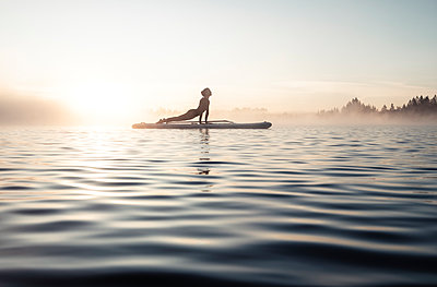 Woman practicing paddle board yoga on lake Kirchsee in the morning, Bad Toelz, Bavaria, Germany - p300m2156797 von Wilfried Feder