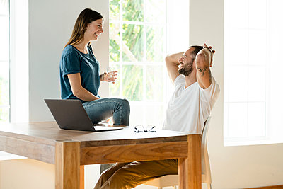 Happy couple with laptop in home office in modern living room - p300m2180607 by Steve Brookland