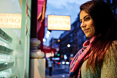 Smiling woman looking at store display in city - p300m2273670 by Angel Santana Garcia