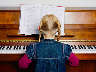 A little girl playing a piano, rear view, portrait - p3018689f by Paul Hudson