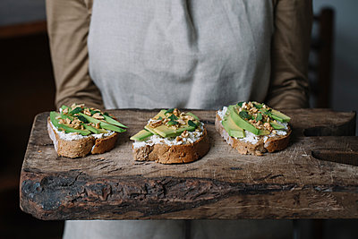 Woman holding chopping board, with ricotta, avocado and walnut bruschetta on top, mid section - p429m1477692 by Alberto Bogo