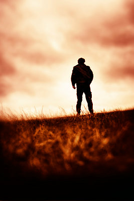 Silhouette of man standing in grassy field - p597m2222394 by Tim Robinson