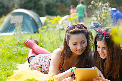 Teenage Girls Lying on Grass Using Tablet - p669m806293 by Jutta Klee photography