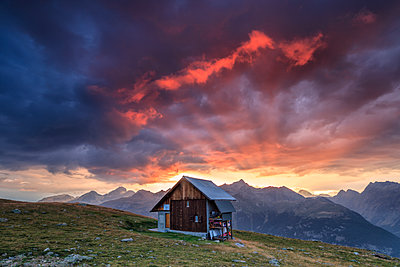 Wooden hut framed by fiery sky and clouds at sunset, Muottas Muragl, St. Moritz, Canton of Graubunden, Engadine, Switzerland, Europe - p871m1478739 by Roberto Moiola