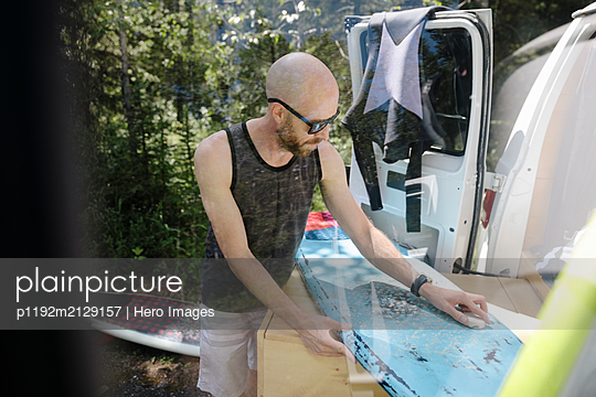 Male surfer waxing surfboard at back of camper van - p1192m2129157 by Hero Images