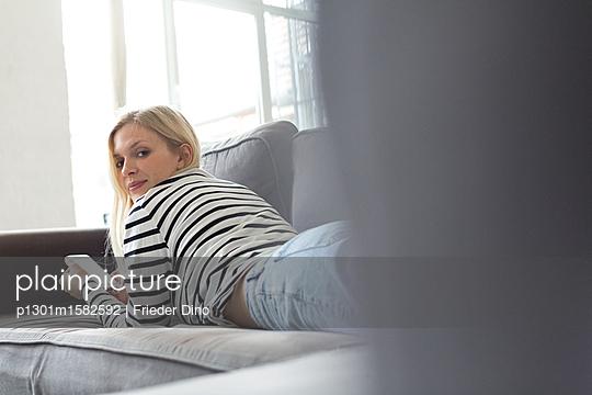 Junge Frau mit Smartphone auf dem Sofa - p1301m1582592 von Delia Baum