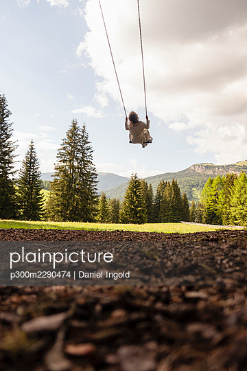 Girl on rope swing in forest - p300m2290474 by Daniel Ingold
