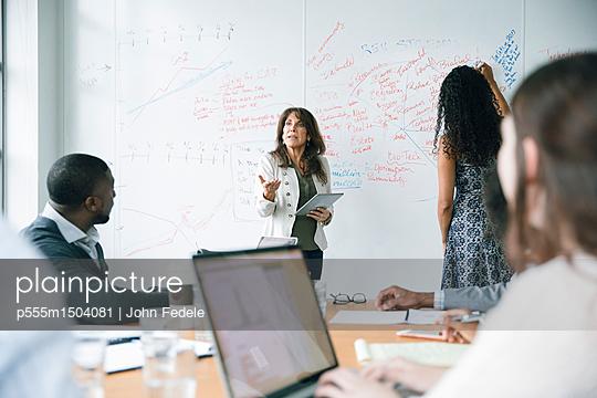 Businesswoman holding digital tablet near whiteboard in meeting - p555m1504081 by John Fedele