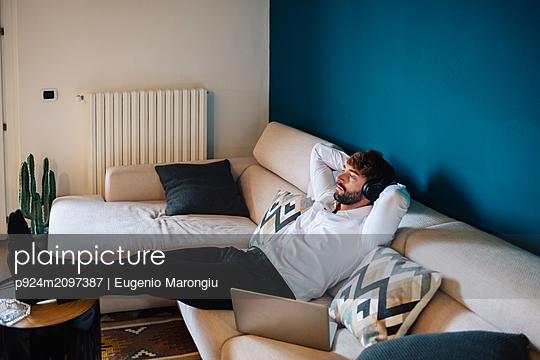 Mid adult man reclining on sofa listening to headphones - p924m2097387 by Eugenio Marongiu