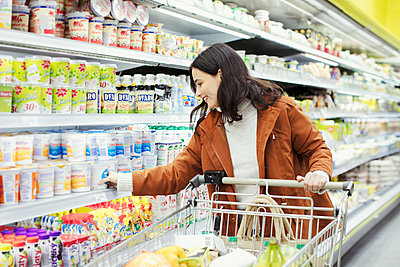 Woman shopping in supermarket - p1023m2187681 by Robert Daly