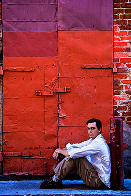 Young man sitting in alley, staring belligerently at the camera. - p1072m874544f by Joseph Shields
