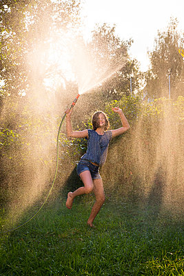 Girl dancing while splashing water with garden hose - p300m1175983 by Larissa Veronesi
