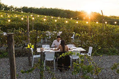 Italy, Tuscany, Siena, young couple having dinner in a vineyard - p300m2058669 by Francesco Buttitta