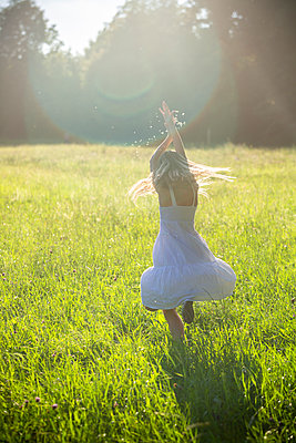 Happy girl dancing on summer meadow at backlight - p300m2062800 by Sandra Roesch