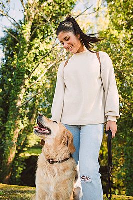 Smiling young woman with her Golden retriever dog in a park - p300m2070699 by Ramon Espelt