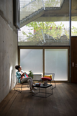 Businesswoman sitting in a loft at concrete wall having a break - p300m2079811 by Florian Küttler