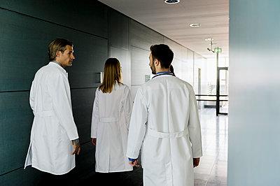 Male and female doctors walking in corridor at hospital - p300m2281512 by Buero Monaco