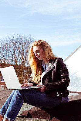 Junge Frau mit Laptop auf Dach - p432m1220799 von mia takahara