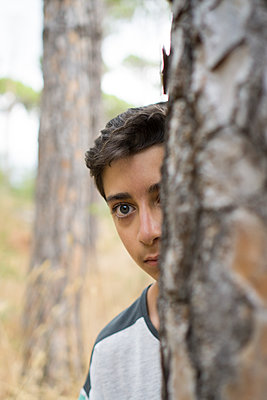 Scared boy behind a tree  - p794m2031649 by Mohamad Itani