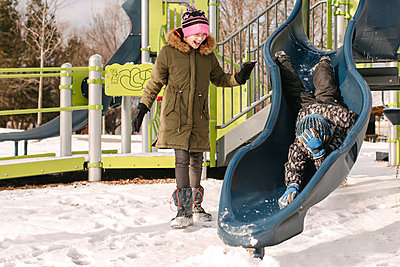 Girl watching brother headfirst on playground slide in snow - p924m2074804 by Viara Mileva