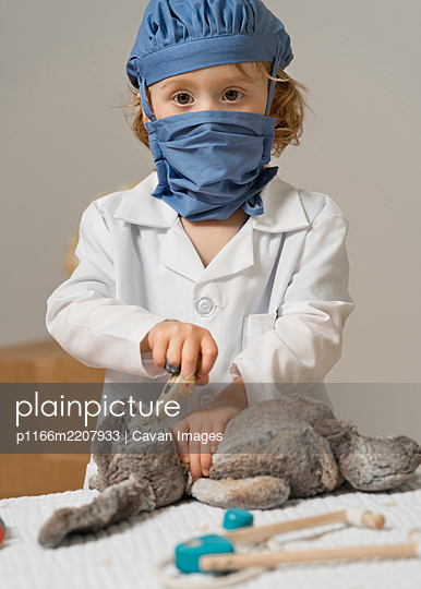 young child in medical PPE examines a plush toy rabbit by taking it's temperature with thermometer - p1166m2207933 by Cavan Images