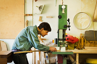 A craftsman holding a piece of wood and using a mortice machine. - p1100m1522484 by Mint Images