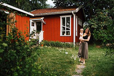 Mother with baby in garden - p312m2280637 by Stina Gränfors