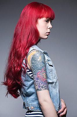 Young woman with long red hair and tattoos, profile - p429m824483 by Leland Bobbe