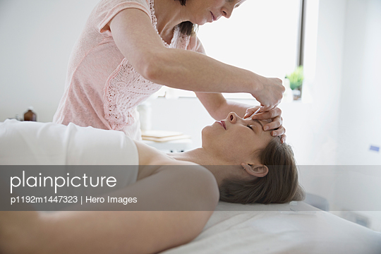 Female acupuncturist inserting needle into forehead of woman on massage table