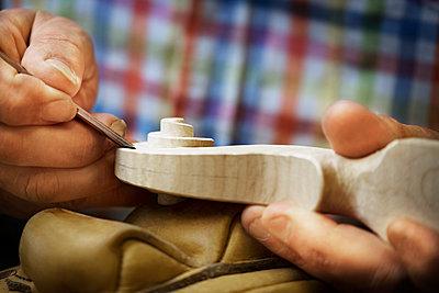 Cropped image of craftsman carving wood - p1166m1163575 by Cavan Images