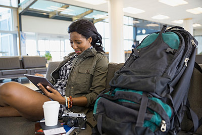Woman with backpack and digital tablet in airport - p1192m1023656f by Hero Images